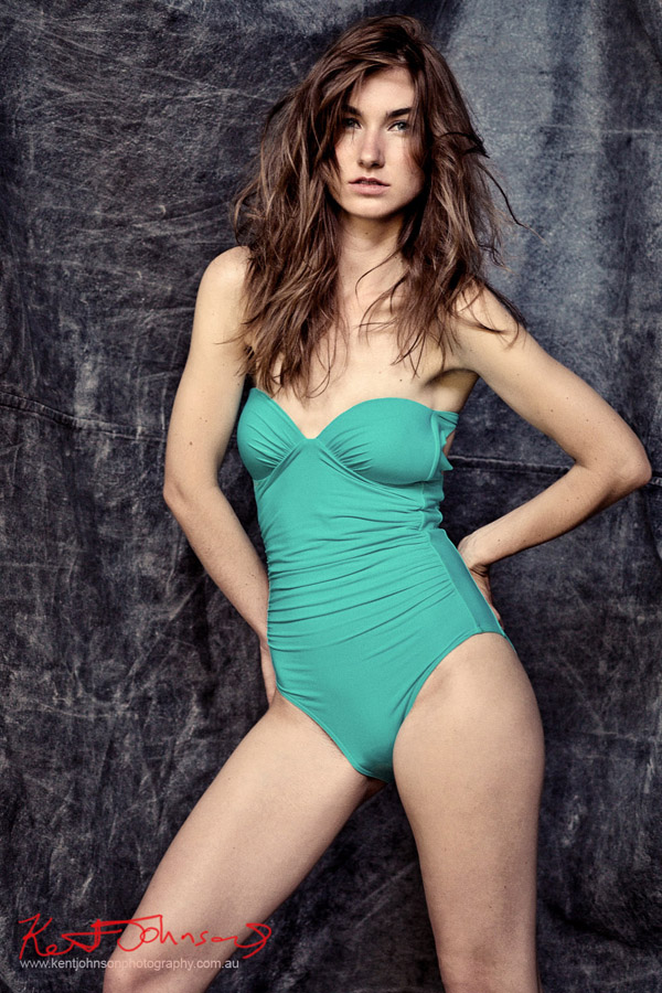 Model in a green one-piece swimsuit photographed in the studio against a black background for a modelling portfolio. Photography By Kent Johnson.