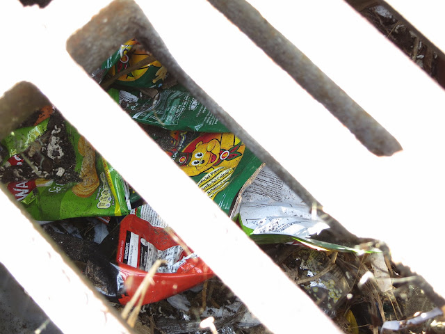 Bright wrappers and other rubbish seen through the cover of a drain in a gutter.