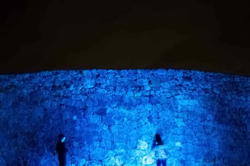 tourists and castle walls at night