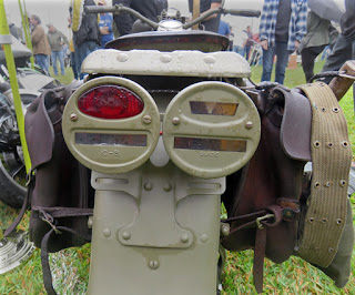 Regular and hooded tail lights on back of military motorcycle.