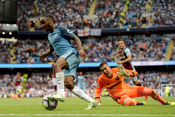 Manchester City's English midfielder Raheem Sterling goes around West Ham United's Spanish goalkeeper Adrian to score his second goal of the match.