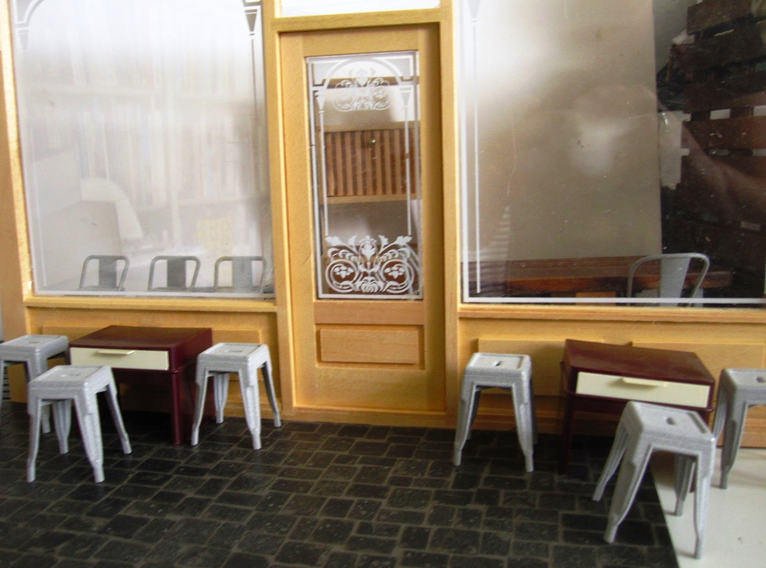 Mock up of the front of a modern dolls' house miniature cafe, showing the shop front and several tables and unpainted cafe chairs.