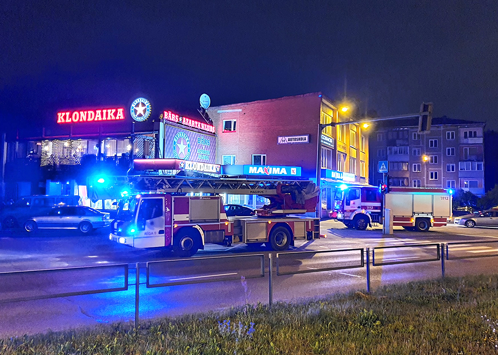 Ugunsdzēsēju auto stāv pie ēkas naktī