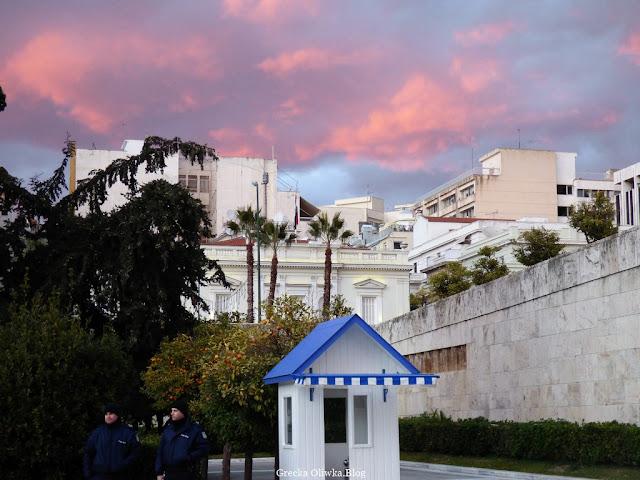 strażnicy w granatowych mundurach, biała budka z niebieskim dachem oraz purpurowe niebo nad Placem Syntagma Ateny Grecja