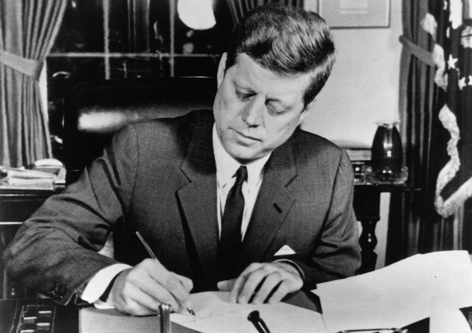 President John F. Kennedy signs a proclamation enacting the U.S. arms quarantine against Cuba, on October 23, 1962.