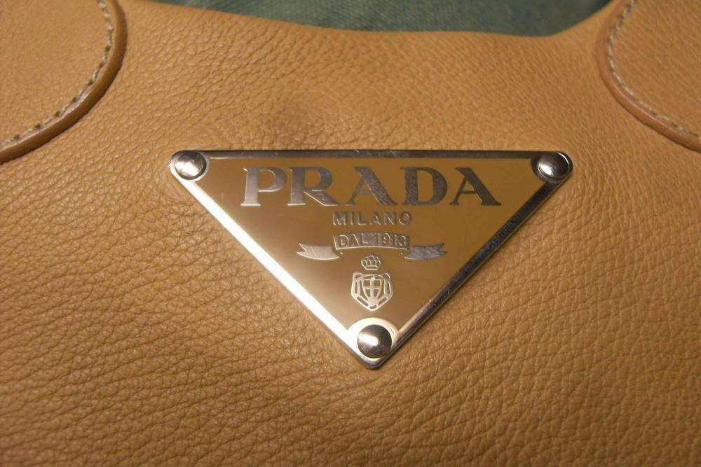 b60337883657f1 Most handbags have the Prada logo outside, usually in the center on the  front of the bag. The logo can vary, but is often the triangle plaque.