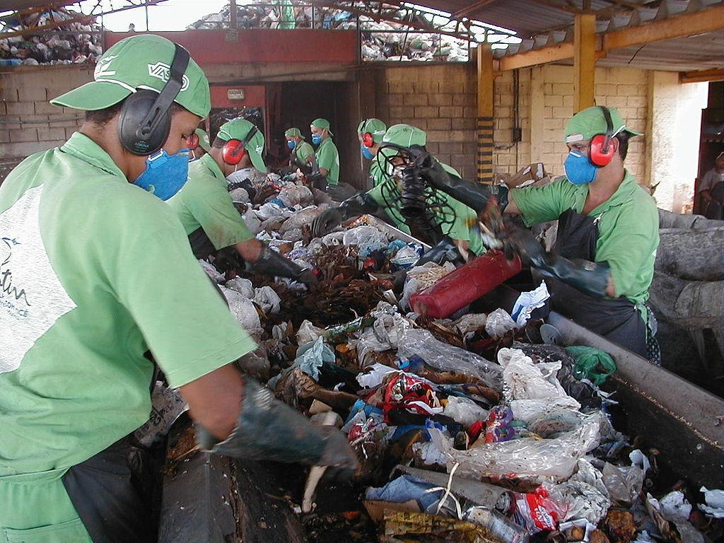 Triagem manual de lixo para reciclagem. Autor: Ignácio Costa. Fonte: https://pt.wikipedia.org/wiki/Ficheiro:TriagemDeLixo.jpg