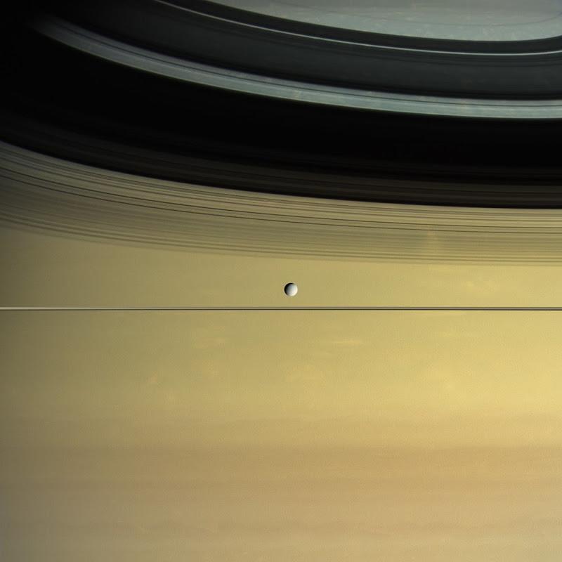 Hình ảnh này từ tàu vũ trụ Cassini của NASA cho thấy hệ thống vành đai của Sao Thổ cùng những đám mây ở thượng tầng khí quyển của hành tinh, trong khi mặt trăng Dione - vệ tinh lớn thứ tư của Sao Thổ - đang quay quanh hành tinh chủ trên quỹ đạo của mình và nằm bên dưới chiếc vành đai. Cassini đã đâm vào hành tinh này vào năm 2017 và kết thúc sứ mệnh của mình, hình ảnh này được chụp vào năm 2015 khi con tàu đang ở độ cao khoảng 800.000 km so với Dione. Hình ảnh: NASA/JPL-Caltech/SSI/Kevin M. Gill.