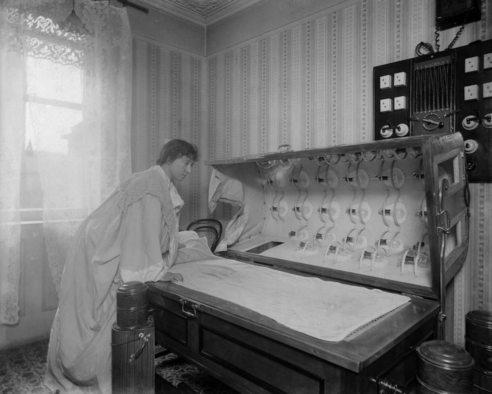 A woman inspects an Electric Bath at the Light Care Institute. The Electric Bath is probably a forerunner of the modern sunbed, although it was more likely used for medicinal reasons. Circa 1900.