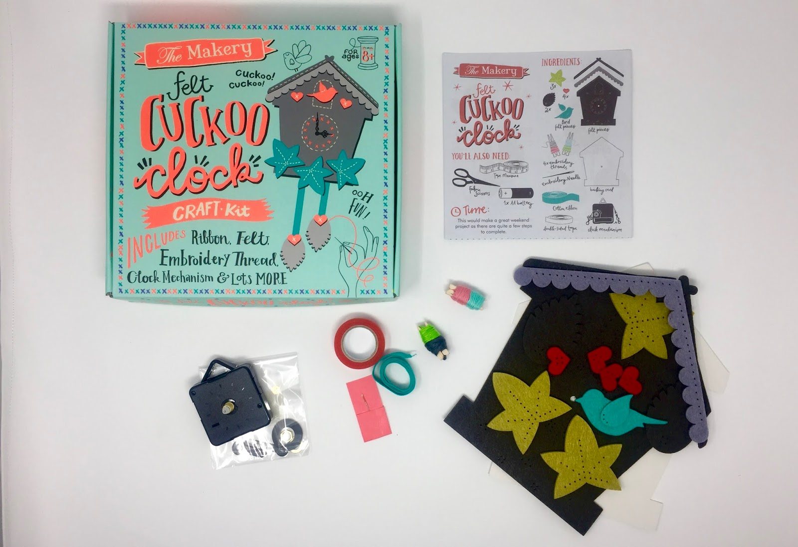 The Makery Felt Cuckoo Clock Craft Kit box next to the contents including instructions, pre cut felt pieces, clock parts, cotton, ribbon and a needle