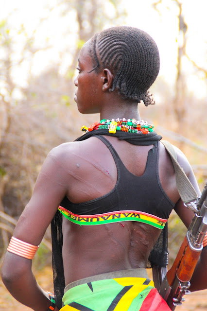 bena tribe girl with lashes on her back carrying a rifle during the bull-jumping ceremony in omo valley, ethiopia