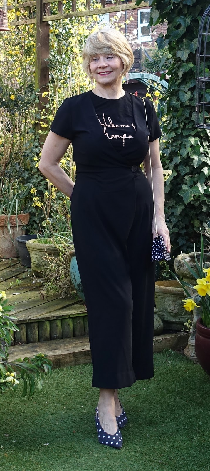 Image showing an over 40s woman wearing a black wrap jumpsuit with a black tee shirt underneath.
