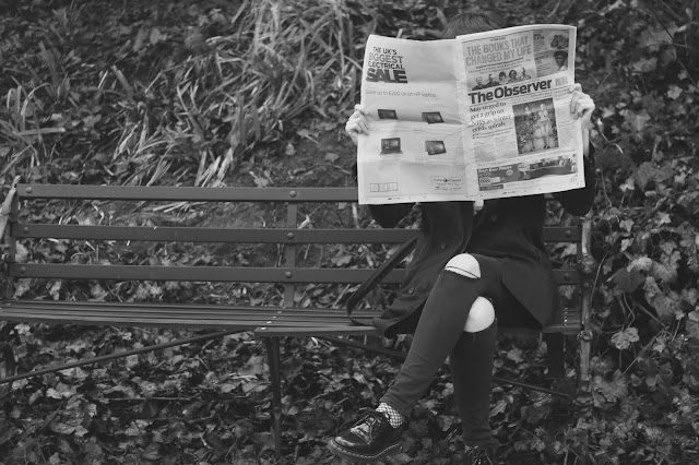Hiding behind a newspaper on a park bench