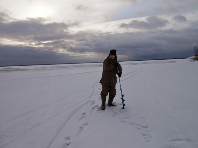 Бурю лунку для рыбалки на озере Иртяш