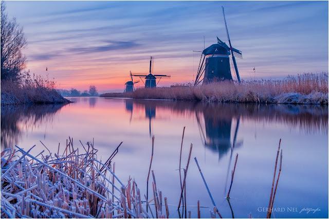 Hollands landschap met reflectie van molens (Kinderdijk) in water