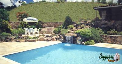 Construção da piscina de concreto com revestimento de azulejo com os muros de pedras ornamentais com execução da cascata da piscina com pedras ornamentais com o piso de pedra São Tomé e execução do paisagismo.