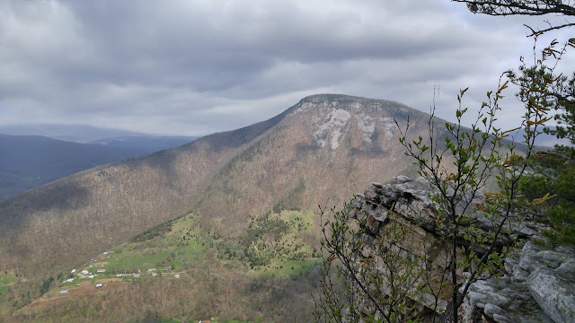 Foreground shows rock outcrop with small trees. In the distance is the rocky crest that makes up the northern side of North Fork Gap. North Fork Mountain, West Virginia.