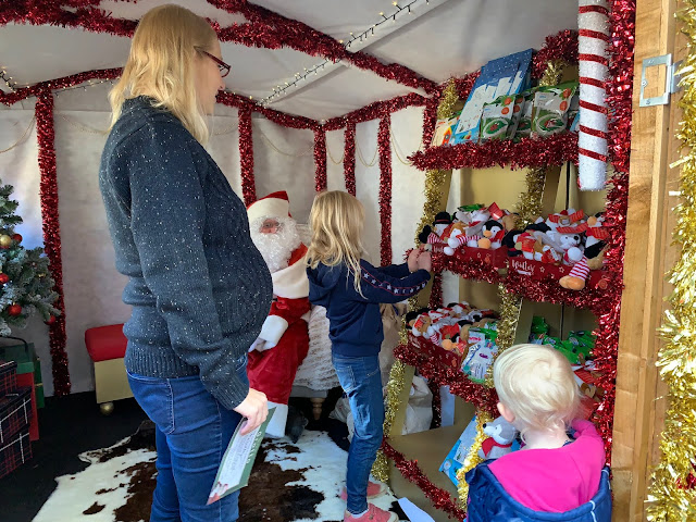 Choosing a present from Father Christmas at Wyevale Garden Centre Grotto