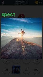 В лучах солнца на высокой горе установлен небольшой крест