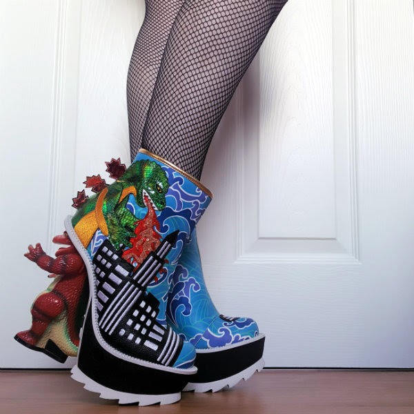 side view of legs wearing blue ankle boots with green dinosaur on side breathing fire and dinosaur shaped heel
