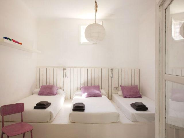 dormitorio con pared de madera de palets y puertas pintadas