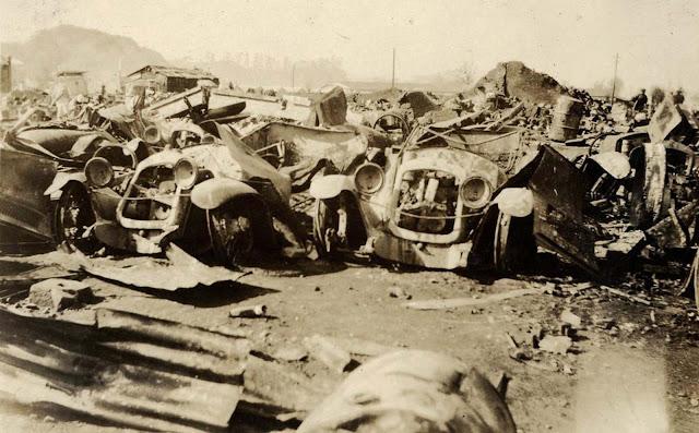 Um local de refugiados.  Talvez um antigo local de refugiados devastado pelo fogo, com carros queimados, pneus, cartuchos e pedaços de entulho.