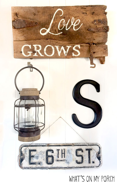gallery wall with love grows wood sign, monogram letter, street sign and lantern