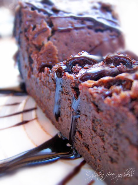 A slice of gluten-free flourless chocolate cake with chocolate sauce.