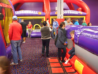 Many adults watching children play on the gigantic inflatables.