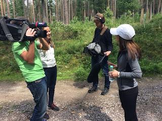 Ein Kamerateam interviewt eine junge Frau. Der Tonmann hat eine Tonangel in der Hand.