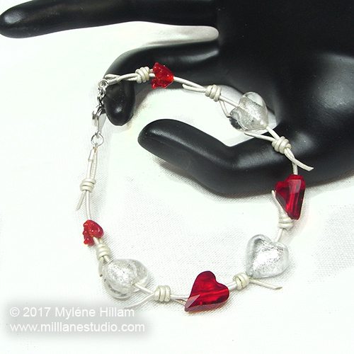 White leather faux barbed wire bracelet strung with red crystal hearts and pearl lampwork heart beads