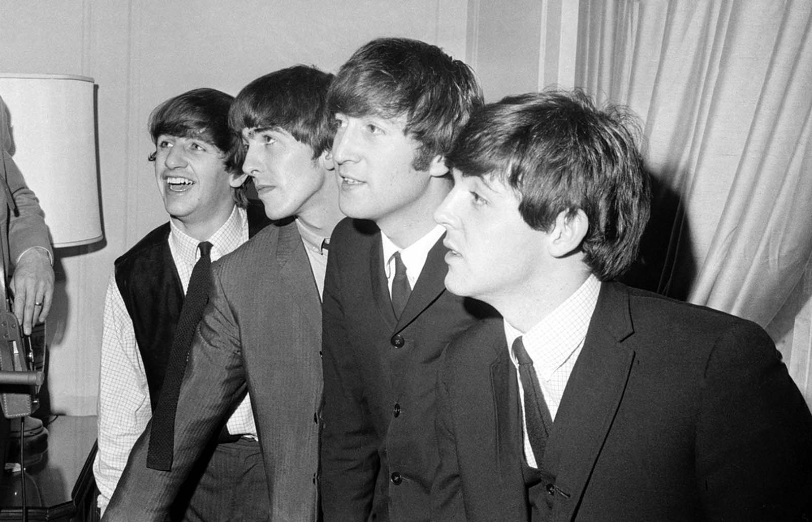 The Beatles, from left, Ringo Starr, George Harrison, John Lennon and Paul McCartney, in their New York hotel after their arrival in the U.S. on February 7, 1964. The British rock group, on their first American tour, was pelted with jelly beans and candy kisses by screaming teen-age fans.