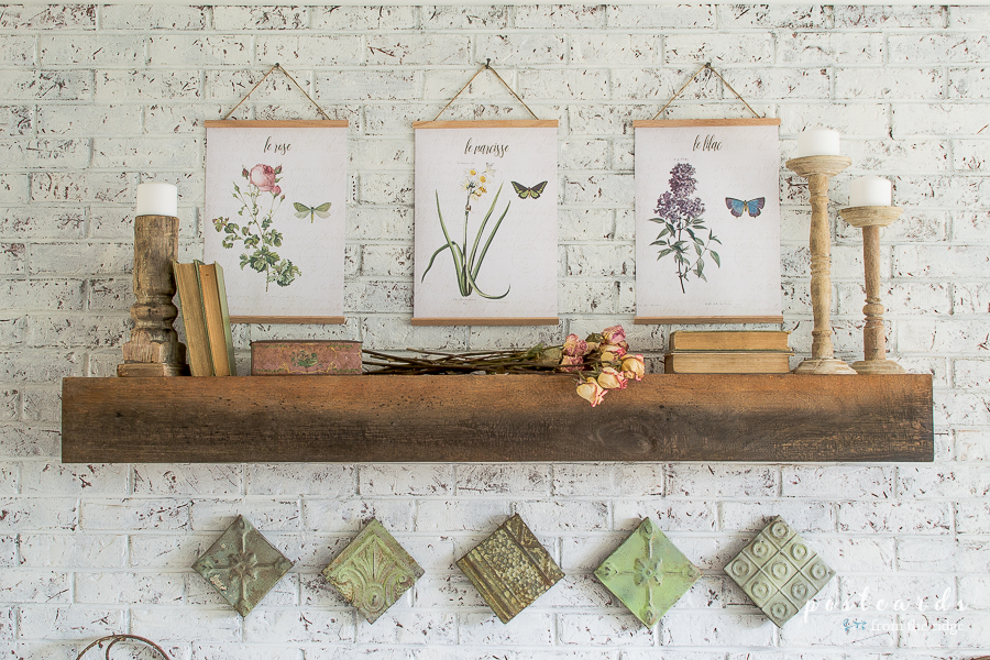 fireplace mantel with botanical floral prints and vintage decor