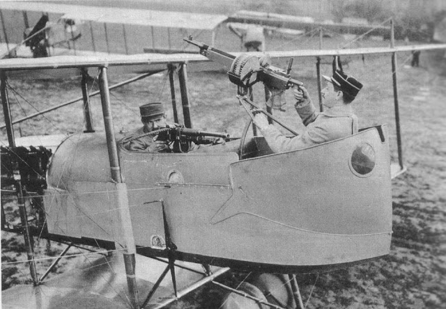 French pilot and observer, sitting in a biplane, demonstrate arc of machine gun fire. The pusher planes made front mounted machine guns impossible. Dogfights and other stories of pilots. marchmatron.com