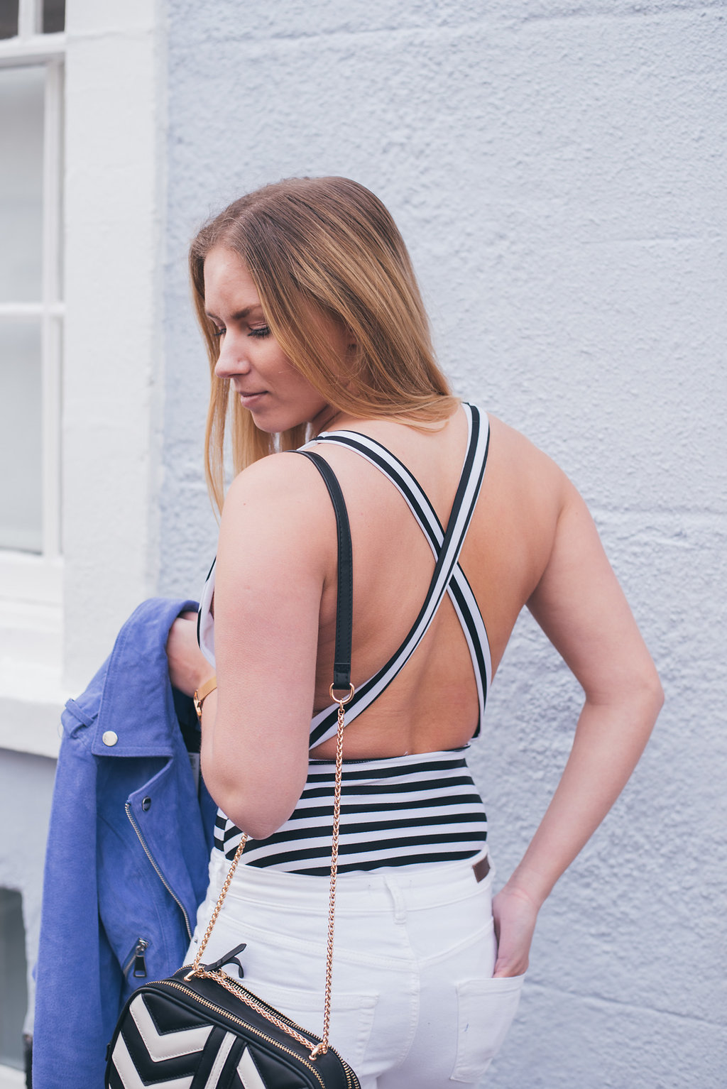 Back of striped swimsuit with blue suede biker jacket and Accessorize bag over shoulder