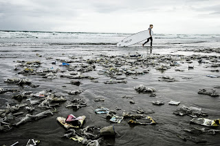 Ironic picture of nasty plastic trash on a beach with a plastic surfboard