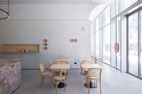Ein Café mit hellgrauen Wänden und hellen Holzmöbeln