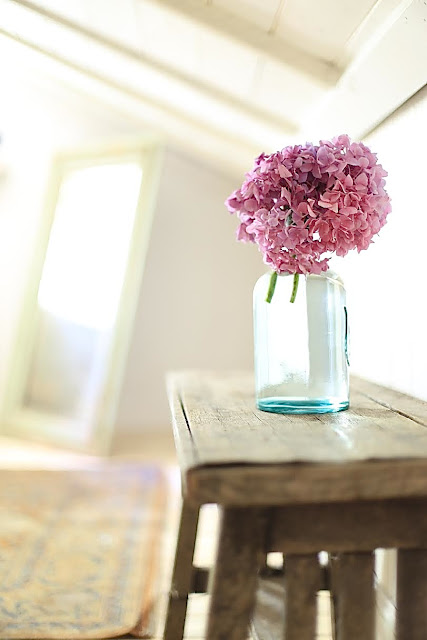 bench with glass bottle and flowers