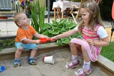Kinder streiten sich im Sandkasten um eine Schippe