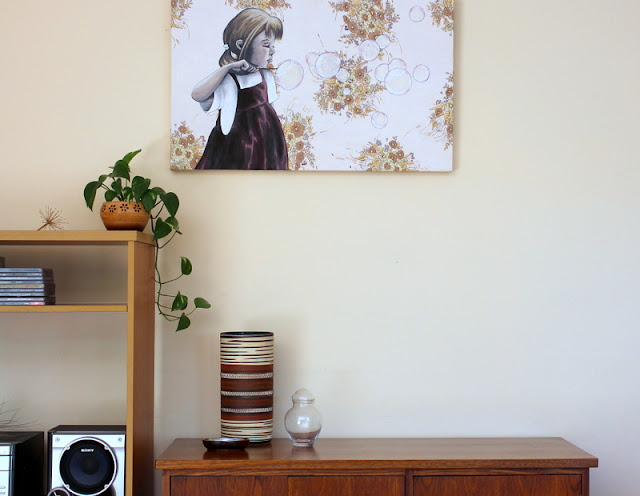 Indoor plant an cupboard  with art work on wall  and vintage vase