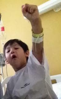 Niño hospitalizado levantando el brazo