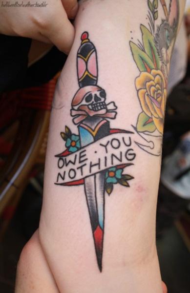 Tatuaje de una daga atravesando una calavera, lo acompaña una frase que dice no te debo nada