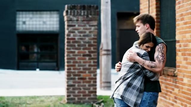 Um casal de jovens se abraçam, no braço do homem tem uma tatuagem imagem do filme Uma Vida Com Propósito
