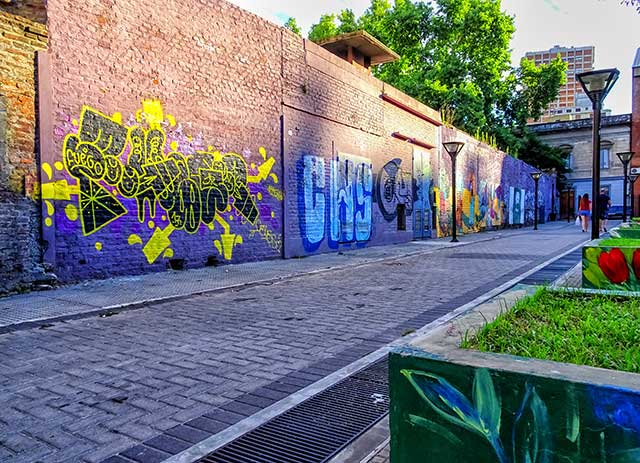 Callle empedrada interna de plaza bordeado ppor un murallon pin tado con grafittis.
