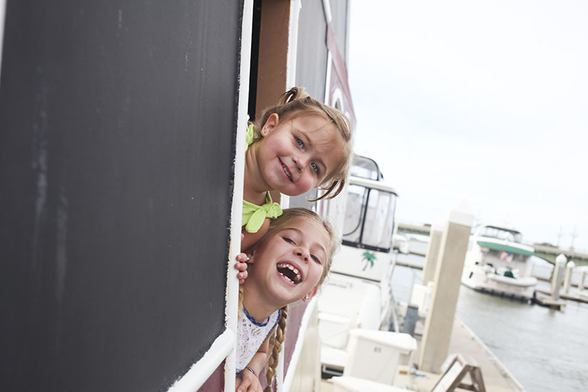 Sisters peeking out the window of a pirate ship.