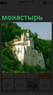 На склоне холма стоит белокаменный монастырь с башнями и крутыми стенами