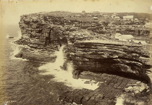 The Gap, Sydney, 188- / photographer unknown. Note: Sydney's most notorious suicide spot, the cliff in front of the buildings, right. On 20 September 1857, the Dunbar was trying to enter Sydney Heads at night in a blinding storm and was smashed on the rocks, lower right. Only one survivor was found the next day. The Dunbar was less than a mile from safety after her more than 10,000 mile journey from Britain. Children still marvel to the story as they view the anchor now on display on the clifftop walk.