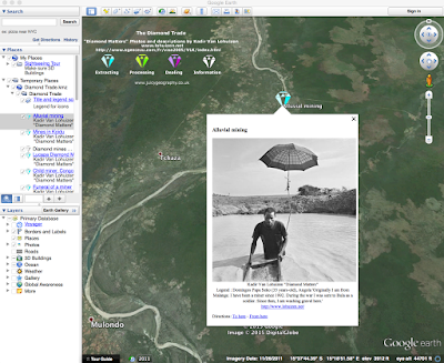 "A screenshot of the Google Earth software. It shows a detailed geographical map of Uganda with diamond-shaped markers. Beneath a marker labeled ""Alluvial mining,"" there is a pop up with a black and white photo of a man in a muddy body of water, sifting gravel with a box. The caption reads: Kadir Van Lohuizen ""Diamond Matters"" Legend: Domingos Papa Seko (35 years-old), Angola. 'Originally I am from Malange. I have been a miner since 1992. During the war, I was sent to Bula as a soldier. Since then, I am washing gravel here.'"
