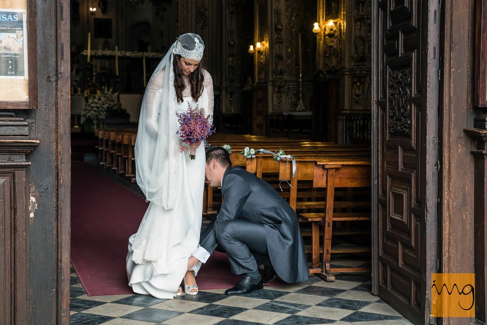 Fotografía de detalle del novio arreglándole el vestido a la novia a la salida de la iglesia