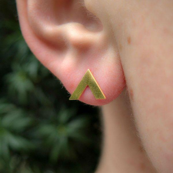 gold V-shaped earring in model's earlobe